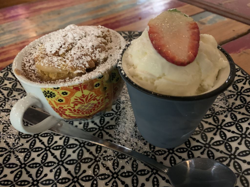 lava cake served in a tea cup with a side of ice cream