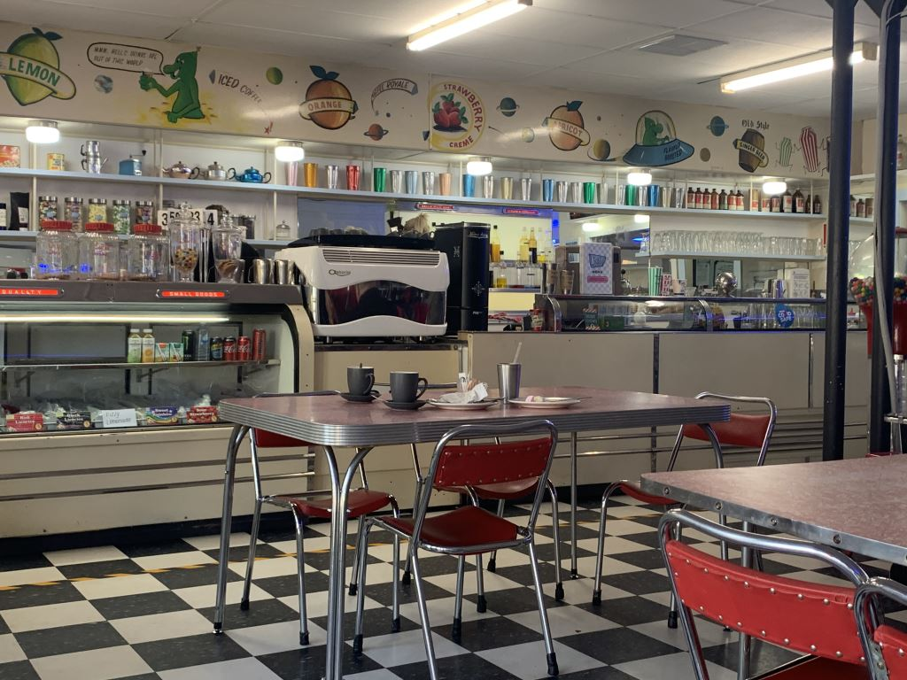 1950s diner with a checked floor and red chairs and tables